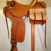 "#2609; 58 Wade Tree, 15 1/2"" seat, wood post horn 2 3/4"" high, 3 1/2"" cap rawhide bound; cantle 4 1/2"" high Cheyenne roll rawhide bound; 7/8 flat plate rigging, 4"" brass stirrups, all rough out , flower carved rear jockeys, rawhide on gullet, bucking rolls, scabbard rings, saddle bags."