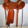 "#2107; Glenn's Wade Tree, 15 1/2"" seat, horn 2 1/2"" high, 3 1/4"" cap rawhide bound, cantle 5"" rawhide bound Cheyenne roll, 7/8 flat plate rigging, tin bound overshoe stirrups, rough-out seat with border stamp, border stamped skirts, fenders, rear jockeys, floral carving in corners, bucking rolls."