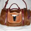 brown hair-on bag with cut-out steer head with black & white hair-on hide behind it